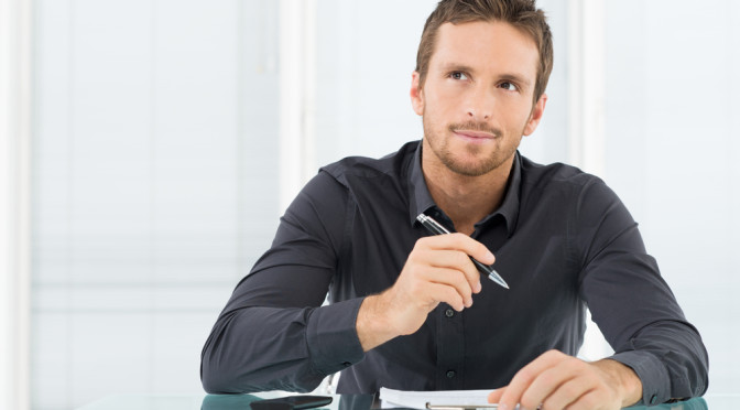 Young Businessman Thinking and Wondering While Writing a Paper